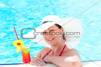 happy young girl with cocktail relaxing by the pool