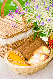 Buns in a wicker basket and a bouquet of field flowers  close-up