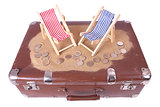 Vintage suitcase with euro coins lie in front of toy beach chair