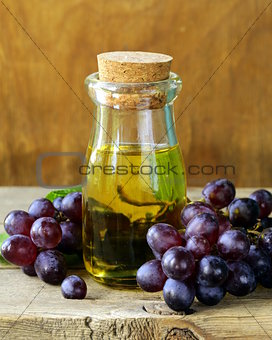 bottle with grape seed oil on a wooden table