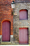 Old vintage brick wall with red wooden doors and windows