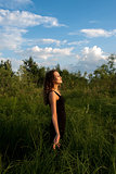 Beautiful girl walks in high grass