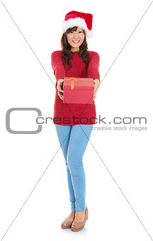 Full body Christmas woman holding gift wearing Santa hat.