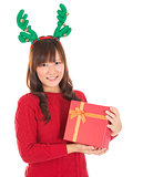 Asian Christmas woman holding gift wearing reindeer horns.