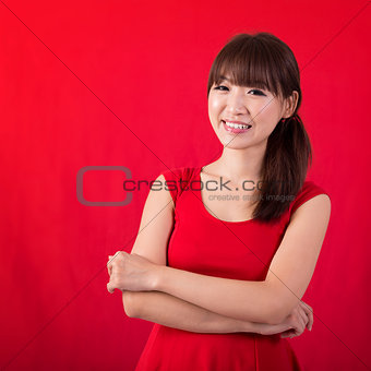 Portrait of cute Asian woman over red background