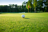 Selective focus view of golf ball on a green with flag