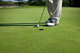 Golfer tapping in short putt