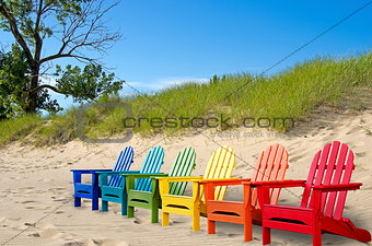 colorful beach chairs in sand