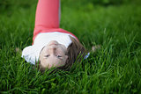 young attractive girl lying on the grass and looking to the camera