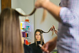 woman in hairdresser shop cutting long hair