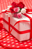 White gift box with red bow and paper flowers
