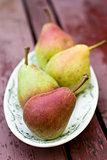 Tasty fragrant pear lying on a white plate