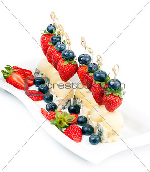 Canapes on a plate with cheese melon and strawberries