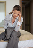 Stressed business woman sitting on bed in hotel room