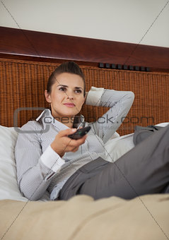 Business woman laying on bed in hotel room and watching tv