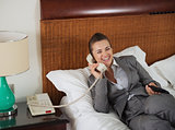 Smiling business woman laying on bed talking phone in hotel room