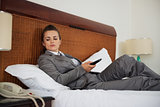 Concerned business woman laying on bed in hotel room and waiting