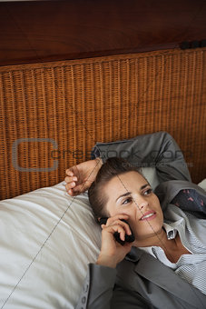 Business woman laying on bed in hotel room and talking cell phon