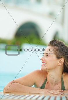Portrait of happy young woman relaxing in pool and looking on co
