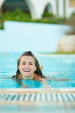 Smiling young woman swimming in pool