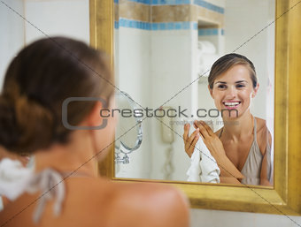 Portrait of happy young woman with towel in bathroom