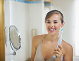Smiling young woman with electric toothbrush