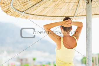 Young woman under umbrella looking into distance . rear view