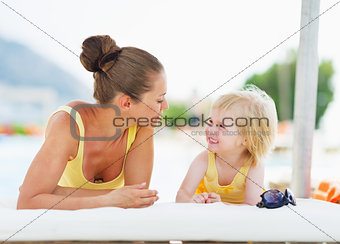 Happy mother and baby playing at poolside