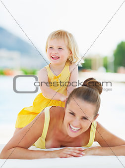 Portrait of happy mother and baby at poolside