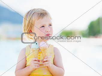Happy baby eating two ice cream horns and looking on copy space