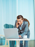 Business woman working with laptop and talking mobile phone on t