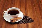Coffee cup with cinnamon stick on wood table