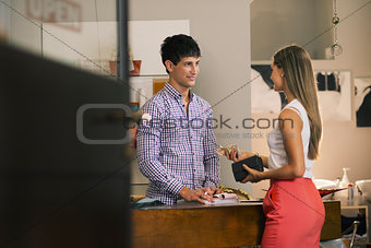 woman paying hairdresser in beauty salon shop