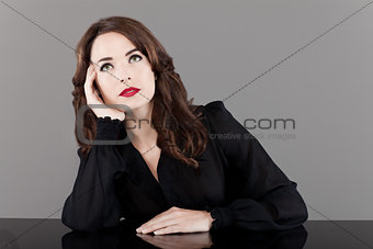 Beautiful middle aged woman with red lips looking up thinking pe