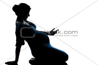 pregnant woman sitting holding babby bottle