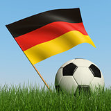 Soccer ball in the grass and flag of Germany