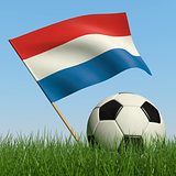 Soccer ball in the grass and flag of Netherlands.