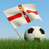 Soccer ball in the grass and flag of Northern Ireland.