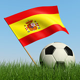 Soccer ball in the grass and flag of Spain.