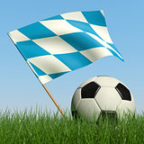Soccer ball in the grass and flag of Bavaria.
