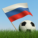 Soccer ball in the grass and flag of Russia.