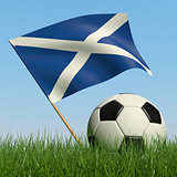 Soccer ball in the grass and flag of Scotland.