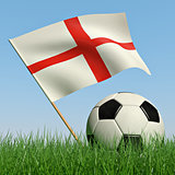 Soccer ball in the grass and the flag of England