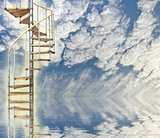 Spiral stairway to heaven glows against blue sky and reflection