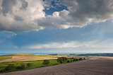 Stunning landscape with stormy sky over rural hills