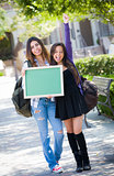 Excited Mixed Race Female Students Holding Blank Chalkboard