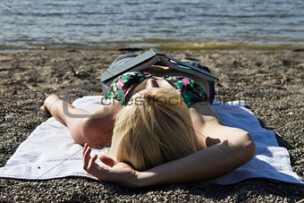 Young woman with a book sleeping on the beach