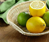 lemons and limes in a wicker basket on the table