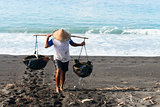 Traditional sea salt production on the volcanic black sand, Bali