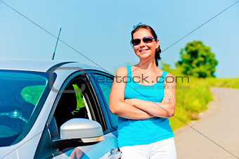 beautiful young woman stands near the new car